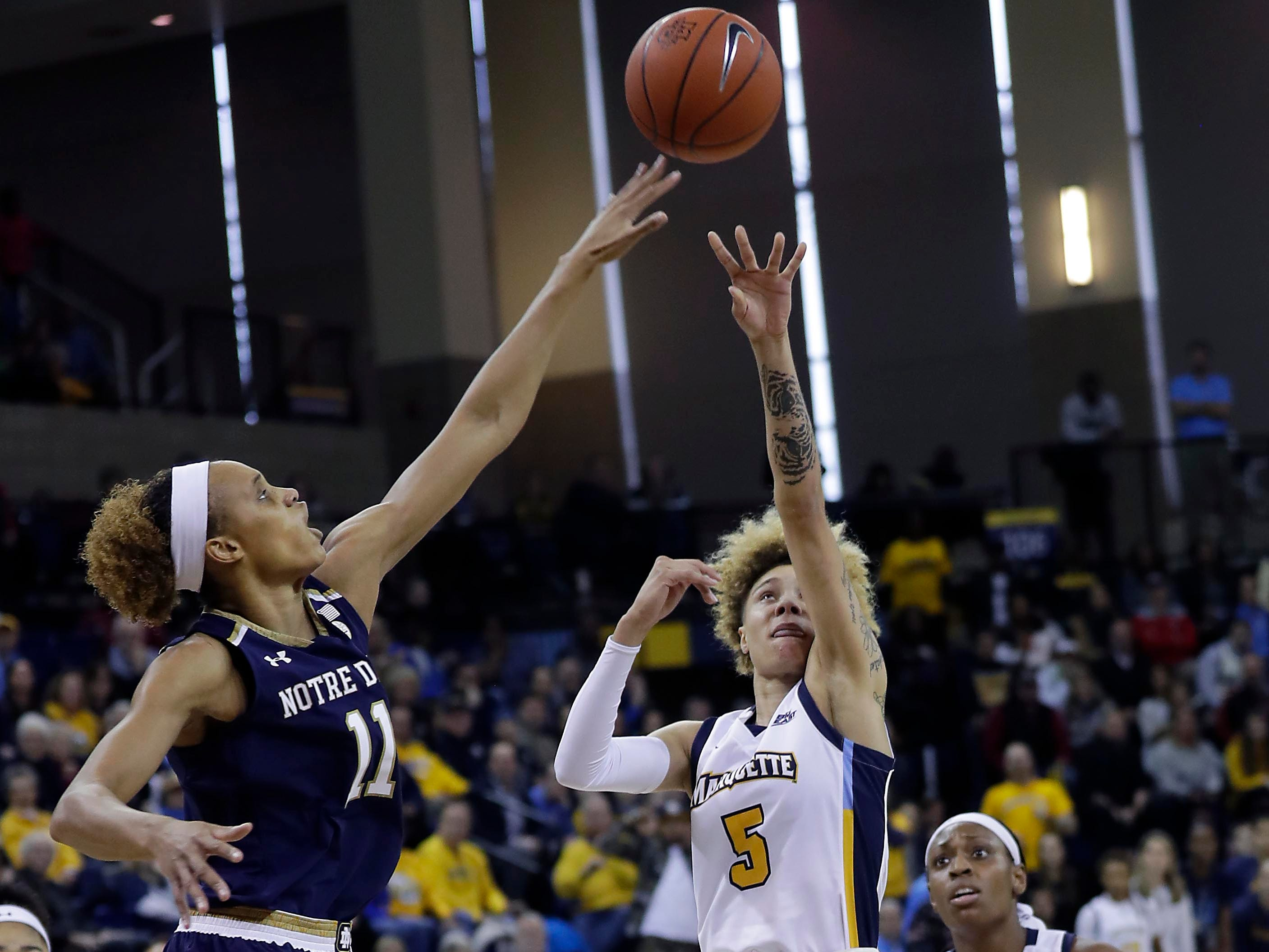 Notre Dame Fighting Irish forward Brianna Turner (11) tips away a shot by Marquette Golden Eagles guard Natisha Hiedeman (5) during the women's basketball  game  between Marquette and Notre Dame. Notre Dame, the the defending national champion, which won the game 87-63, is led by former DSHA star Arike Ogunbowale. MU is also a top-25 team expected to win the Big East.   MILWAUKEE JOURNAL SENTINEL/RICK WOOD ORG XMIT: 20097356A