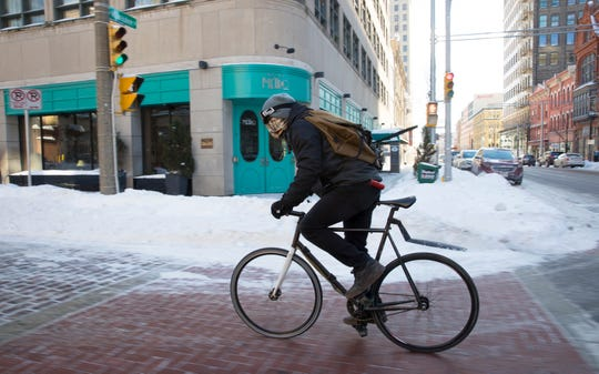 Breakaway Bicycle Courier messenger Corey Wolf was still at work making deliveries Wednesday despite the frigid weather in downtown Milwaukee.