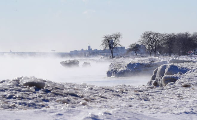 The shores of Lake Michigan are covered from steam rising near ice formations on Bradford Beach in Milwaukee.
