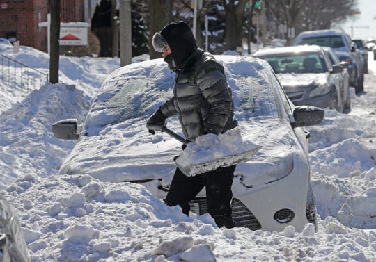Israel Montelongo, a University of Wisconsin-Milwaukee student from Delavan, shovels out his car Wednesday on North Oakland Avenue just north of East Hartford Avenue in Milwaukee.