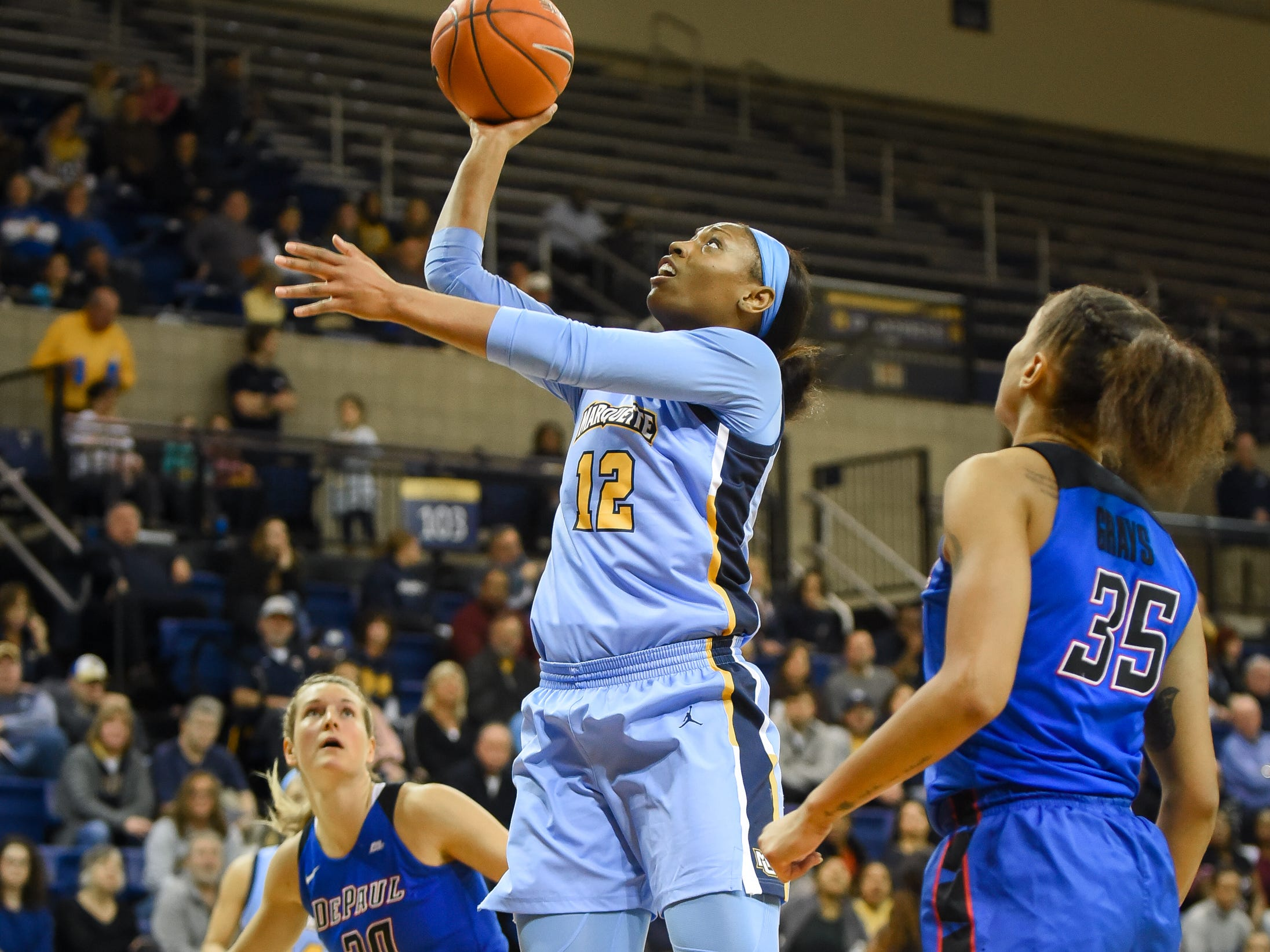 Marquette forward Erika Davenport splits DePaul guard Kelly Campbell (20) and forward Mart'e Grays for a layup in a Big East Conference women's basketball game Friday, January 4, 2019, at the Al McGuire Center on the Marquette campus.