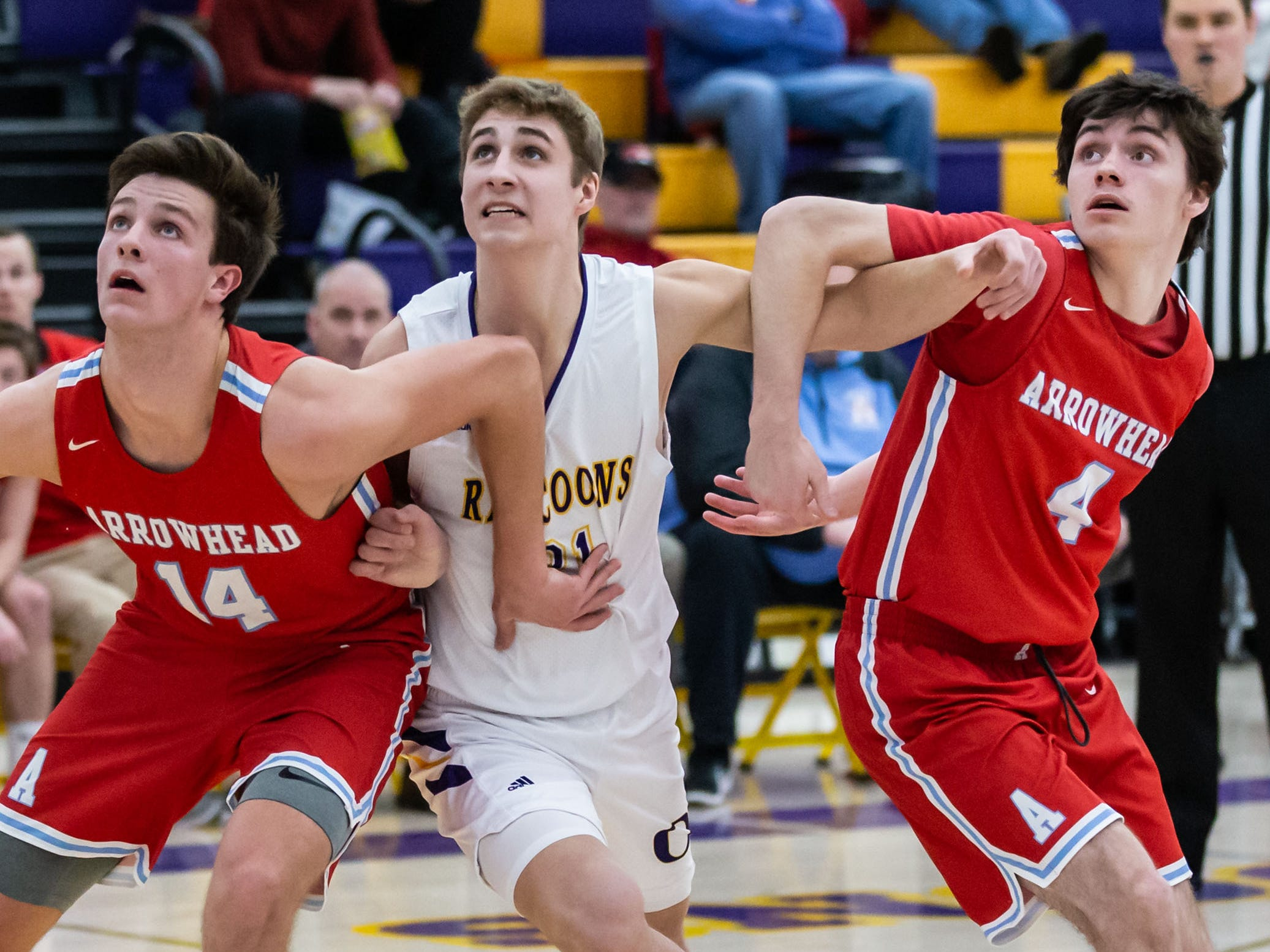 Oconomowoc's Sam Rott (center) gets boxed out by Arrowhead's Carter Gilmore (14) and Chris Burg (4) during the game at Oconomowoc on Tuesday, Jan. 29, 2019.