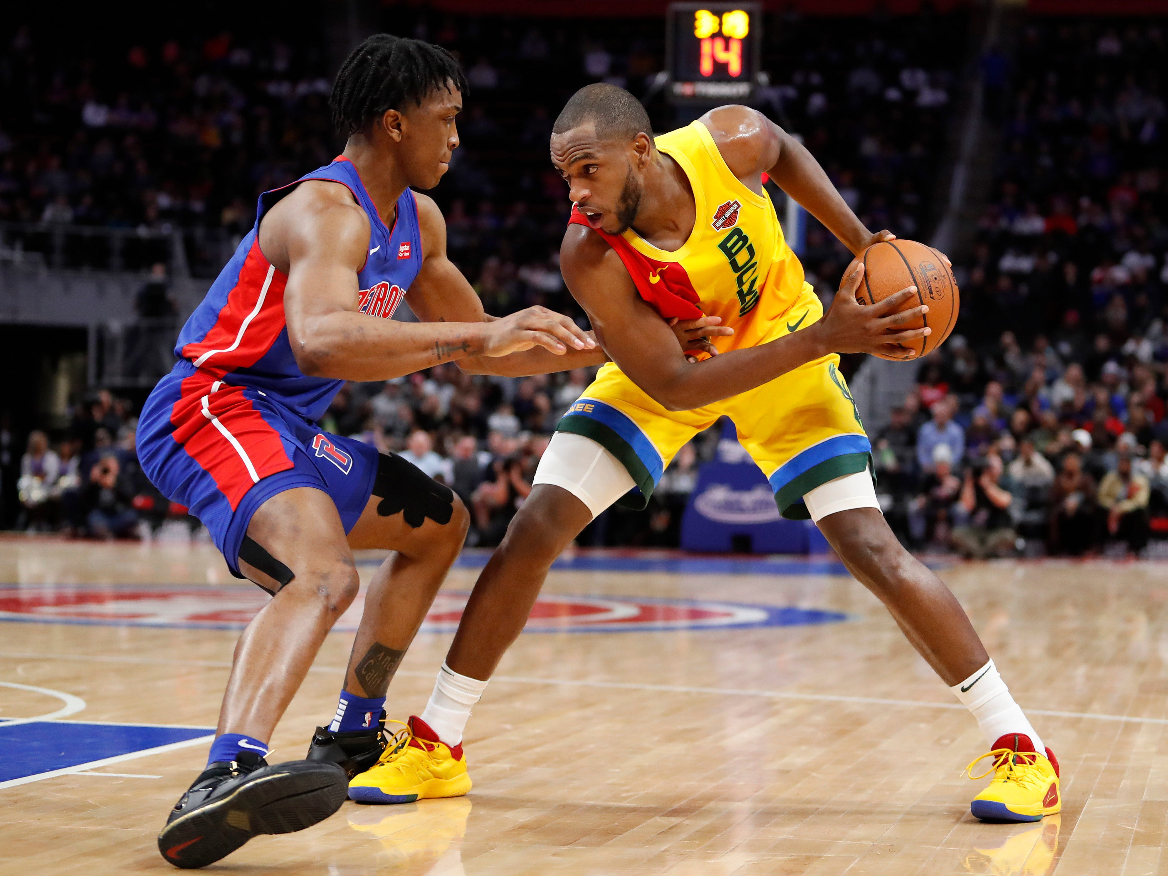 Bucks forward Khris Middleton looks to find a way around Detroit's Stanley Johnson.