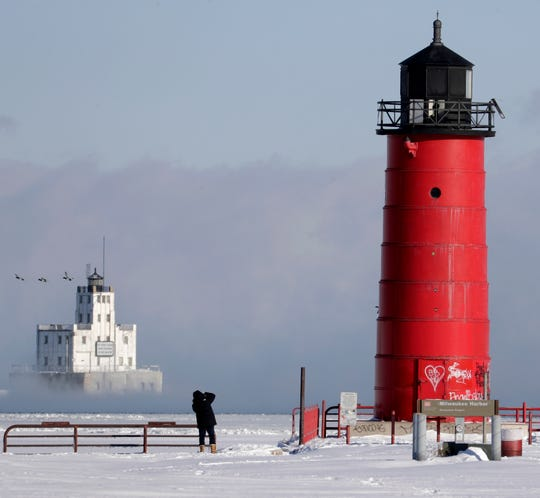 A passerby photographs vapor rising off the lighthouse at the Milwaukee Harbor on Lake Michigan on Wednesday