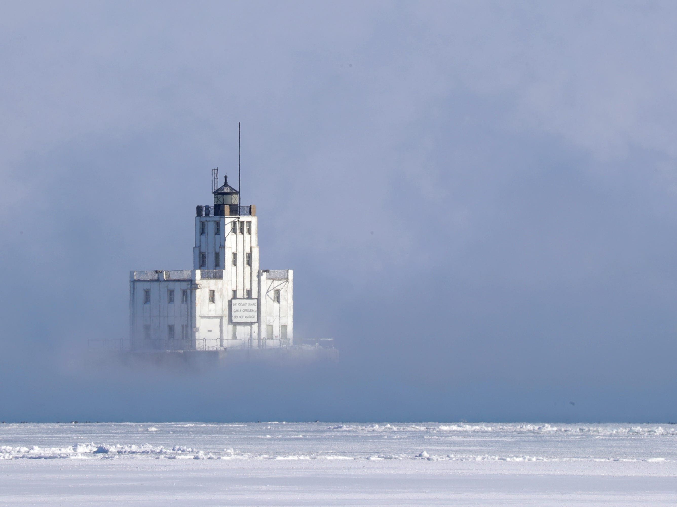 The Breakwater Lighthouse is engulfed in steam on Lake Michigan in Milwaukee.