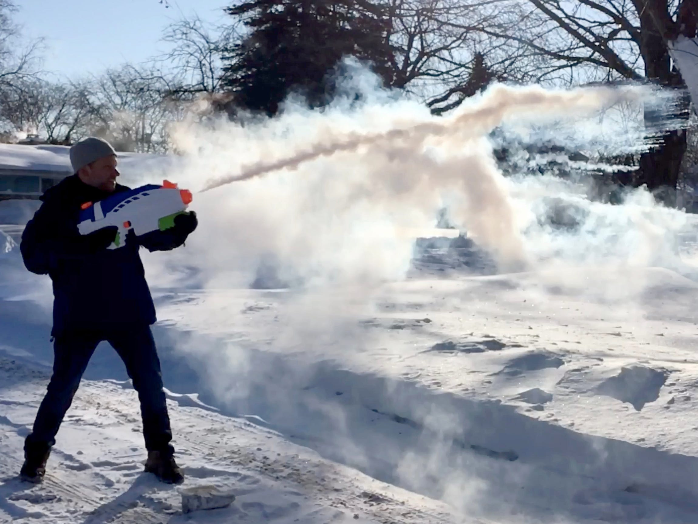 Milwaukee Journal Sentinel photographer Mike De Sisti demonstrates how boiling water reacts to the cold when shot through a Super Soaker in Bayside on Wednesday.