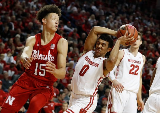 Badgers guard D'Mitrik Trice grabs the rebound depite being bothered by  Isaiah Roby.