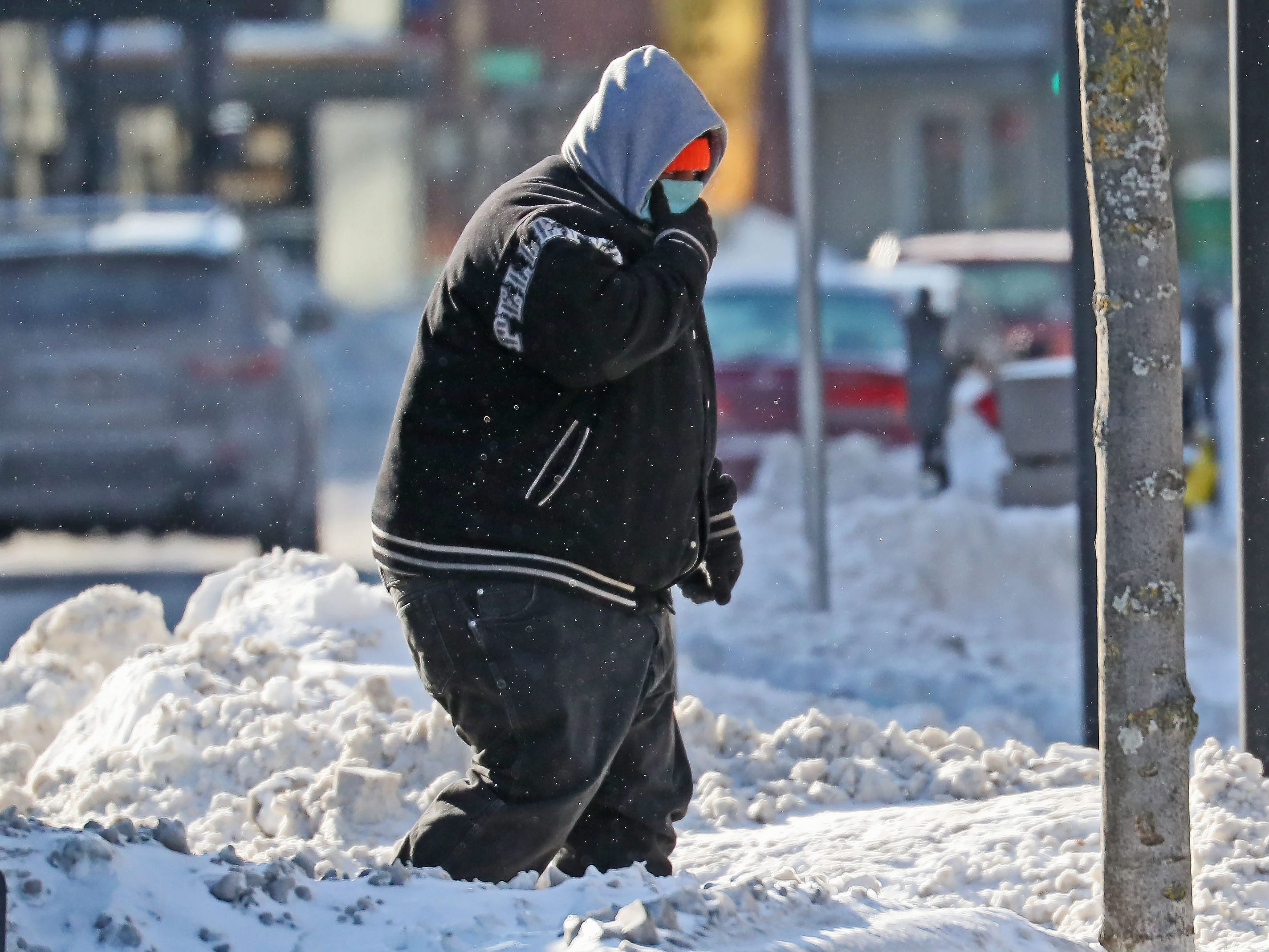 A man covers his face as he heads into the wind along West Kilbourn Avenue in downtown Milwaukee.