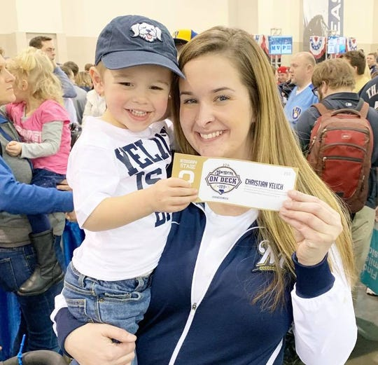 "Three-year-old Carter Gonzalez of Wauwatosa is held by his mom Crystal during the Brewers On Deck event on Jan. 27. The little boy captured attention for wearing a shirt which read, ""Yelich is my BFF"" for his favorite player MVP Christian Yelich."