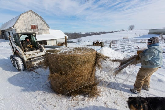 Emily Harris (left) and her wife, Brandi, move a bale of hay Sunday on their small organic dairy farm in Monroe.