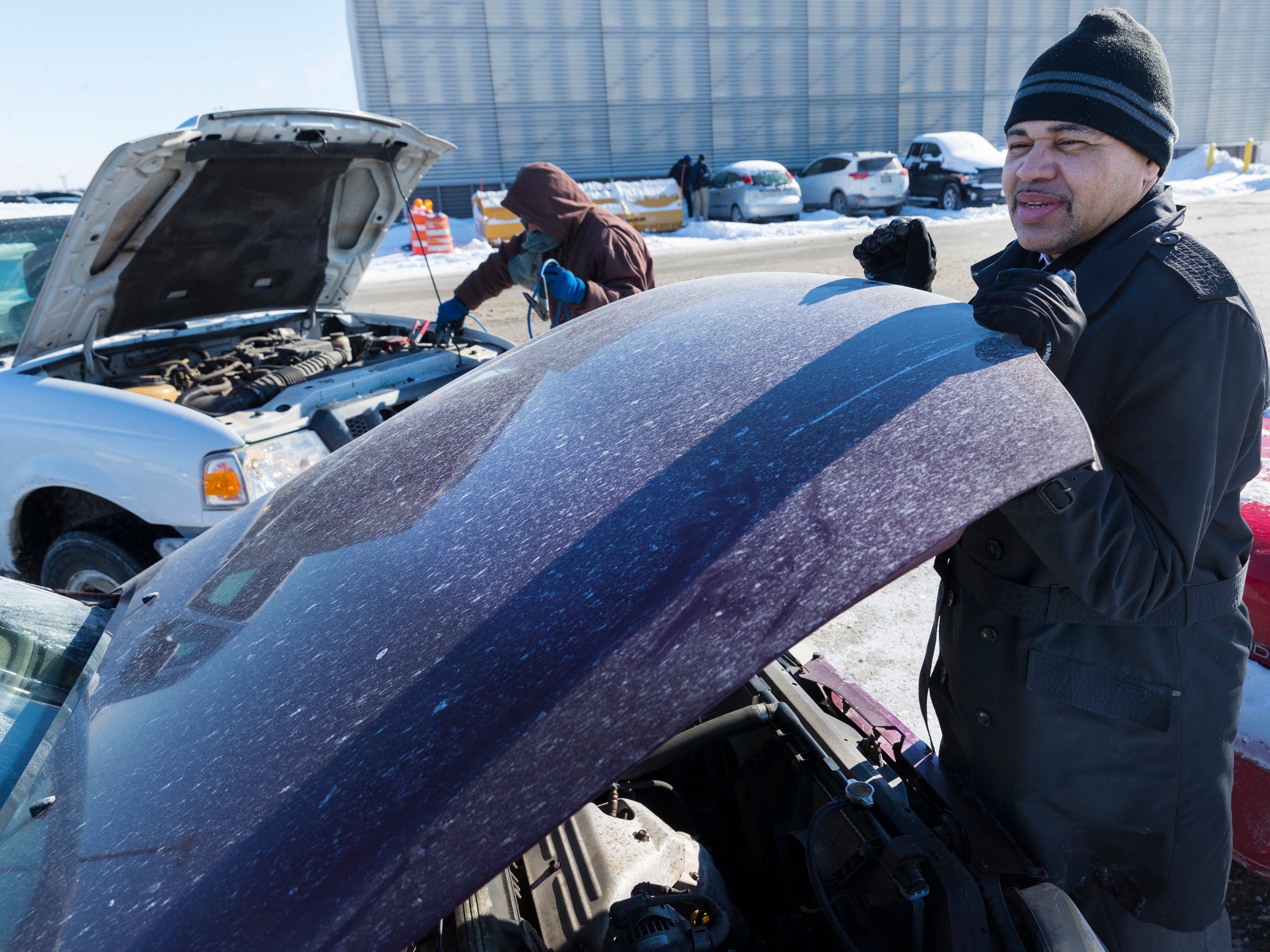 Delta Airlines employee Charles Moreno (foreground) helps Interflight Parking employee Jose Marrero jump-start his car at Mitchell International Airport in Milwaukee.