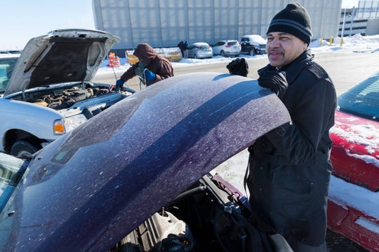 Delta Airlines employee Charles Moreno (foreground) helps Interflight Parking employee Jose Marrero try to jump-start Moreno's car Wednesday at Mitchell International Airport in Milwaukee.