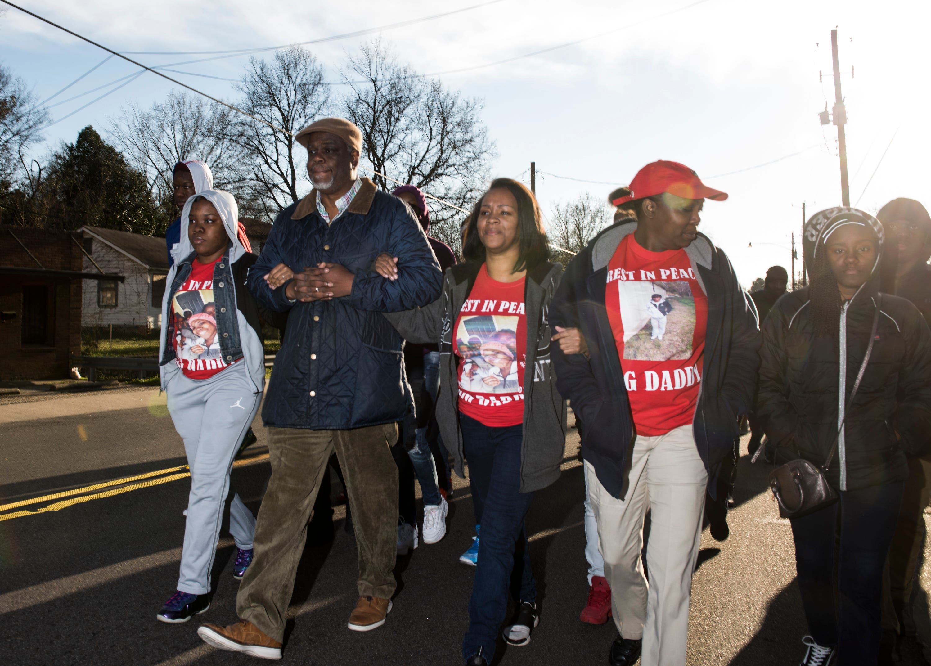 Rev. Ken Austin, middle left, and Bernadette Saunders, middle right, march down Mobile Road during a march against violence in Montgomery, Ala., on Tuesday, Jan. 29, 2019. Jaylan Saunders, 16, was shot and killed Jan. 24 at his home.