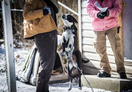 Muncie animal control workers Natalie Beach and Brandy Cox perform a welfare check before removing a dog from a home on E. Charles Street that was left outside in sub-zero temperatures. According to animal control director Melissa Blair, the shelter received nearly 200 calls regarding animals left outside in the cold.