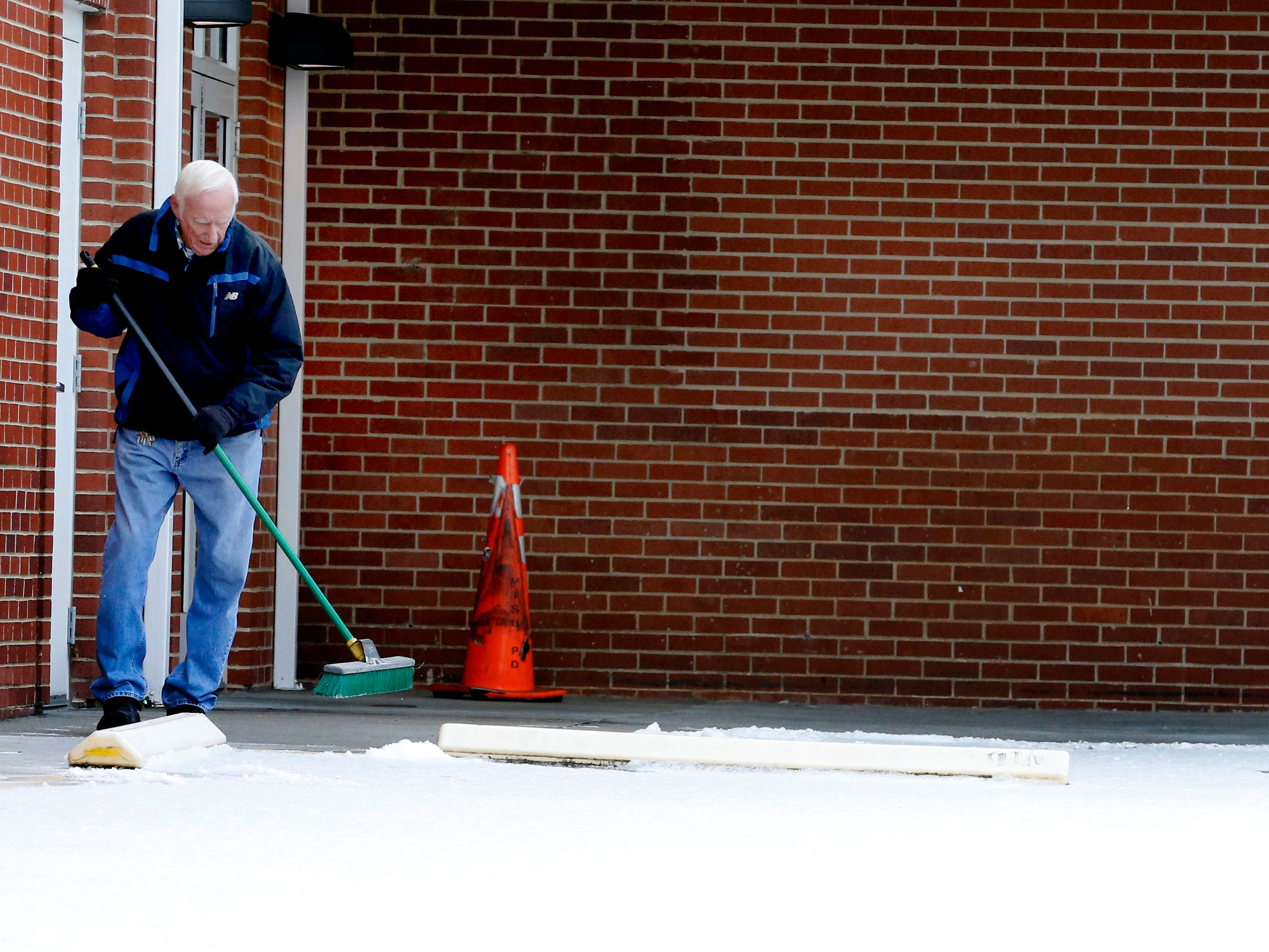Jessie Tenpenny sweeps snow off the sidewalk at Main Street Church of Christ on Wednesday Jan. 30, 2019.