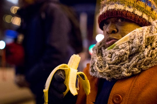 Kimberly Rucker eats a banana given to her by Officer Anthony Cucci during his cold weather checks in Nashville on Tuesday, Jan. 29, 2019.