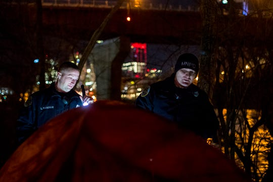 Officers Stephen Waterman and Kevin Johnson check on a tent while performing cold weather checks in Nashville on Tuesday, Jan. 29, 2019.