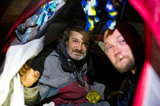 Christopher Thompson, left, and James Emerson, look out of Emerson's tent while Metro Nashville Police officers perform cold weather checks in Nashville on Tuesday, Jan. 29, 2019.