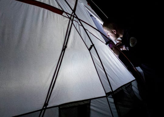 A tent is illuminated by a flashlight while Metro Nashville Police officers perform cold weather checks in Nashville on Tuesday, Jan. 29, 2019.