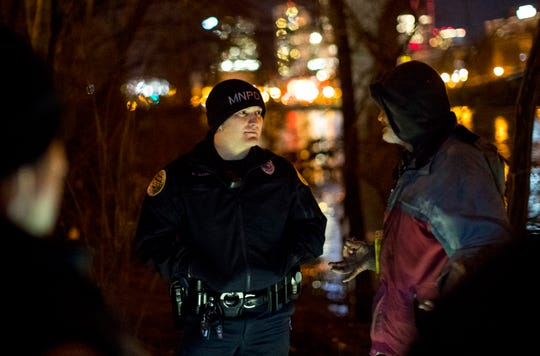 Officer Kevin Johnson speaks with Christopher Thompson while Metro Nashville Police Officers perform cold weather checks in Nashville on Tuesday, Jan. 29, 2019.