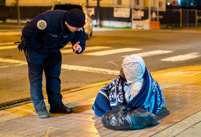 Officer Anthony Cucci asks Eugene Martin if he would like a ride to a shelter or a warming center during cold weather checks in Nashville on Tuesday, Jan. 29, 2019. Martin was lying on a vent which provided some warmth.