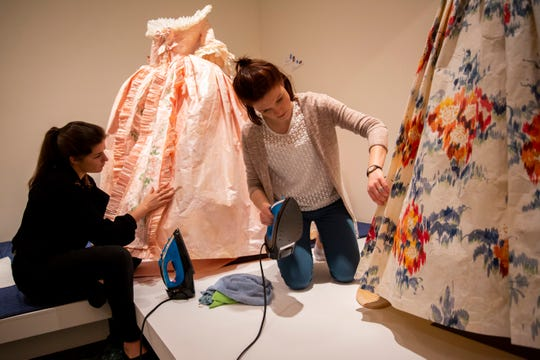 Eleonore Dierick, left, and Kelly Brion, right, of Brussels, Belgium, iron paper dresses by Isabelle de Borchgrave at Artis-Naples in Naples, on Wednesday, January 30, 2019.