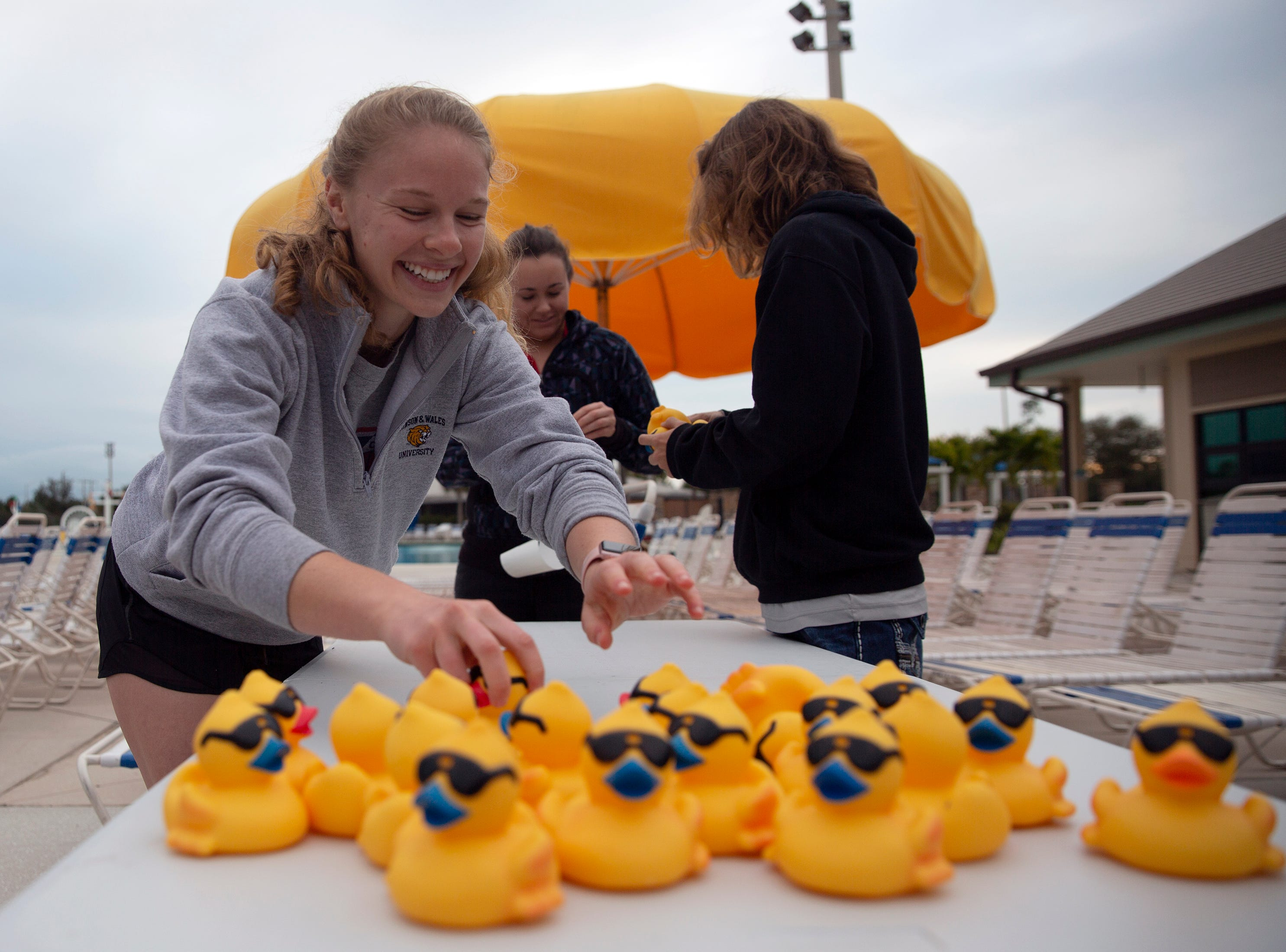 Greer Burcky, left, Kelly Heinemeyer and Ian Hughes tag rubber ducks, Wednesday, Jan. 30, 2019, at the North Collier Regional Park in East Naples.