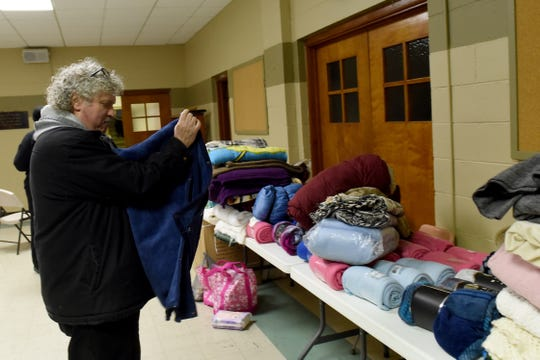 Chris Gargus folds blankets donated to Central Christian Church for use during the polar vortex on Tuesday night. The Newark church opened its doors as a temporary shelter for those in need of a warm place to sleep. The church will also be opened Wednesday night starting at 4 p.m. with doors closing at 9 p.m. for those staying overnight. The warming Center will end at 9 a.m. on Thursday.