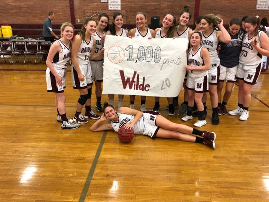 Courtney Wilde (with ball) celebrating her career milestone for Nutley girls basketball with teammates.