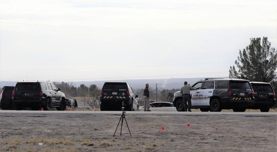 About mid-afternoon, authorities investigate a site north of the Doña Ana Exit of Interstate 25 on Wednesday, Jan. 30, 2019, where a dramatic police pursuit ended earlier in the day. State police have said an officer fired a weapon, but the suspect, who was driving a car whose top is seen center frame, was not struck.