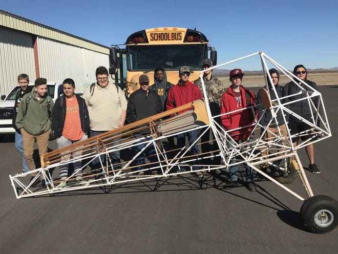 """Mayfield High School students pose with a donated """"Baby Ace"""" fuselage."""