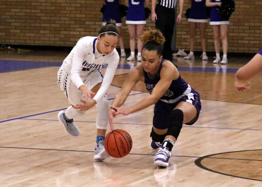 Carlsbad's Baylee Molina, left, and Clovis' Antanishwa Molett, right, fight for a loose ball during their Jan. 29 game. Molett has scored 21 points for the Lady Wildcats in its three district games.