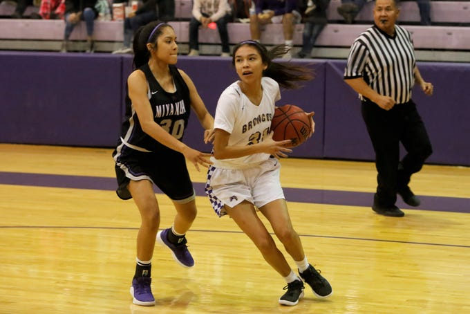 Kirtland Central's Tiajhae Nez drives to the basket against Miyamura's Malia Ukestine during Tuesday's District 1-4A game at Bronco Arena in Kirtland.