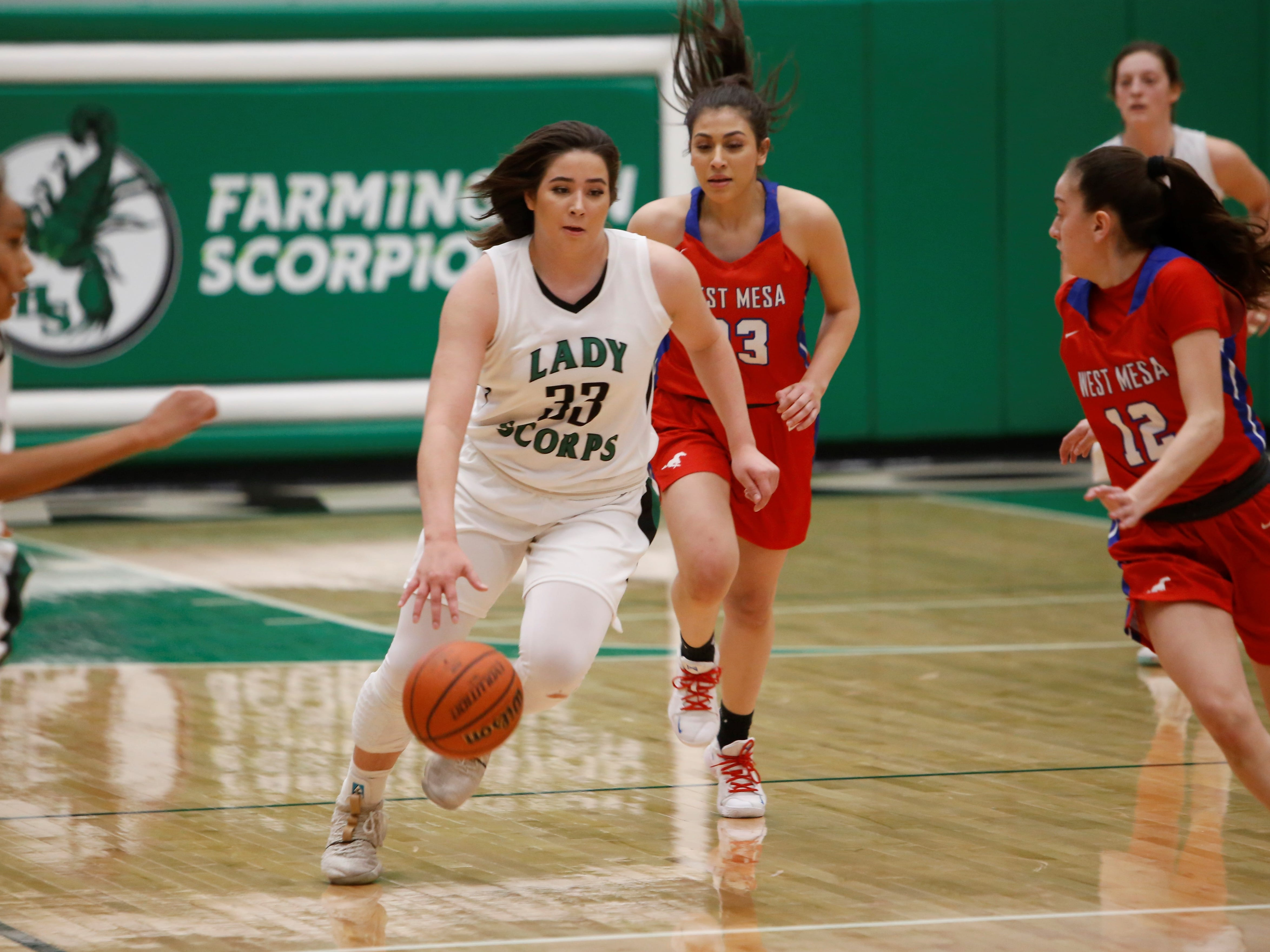 Farmington's Chloe Finch drives down the floor in transition against West Mesa's Jaden Castellano (23) and Maiah Rivas (12) during Tuesday's District 2-5A game at Scorpion Arena in Farmington.