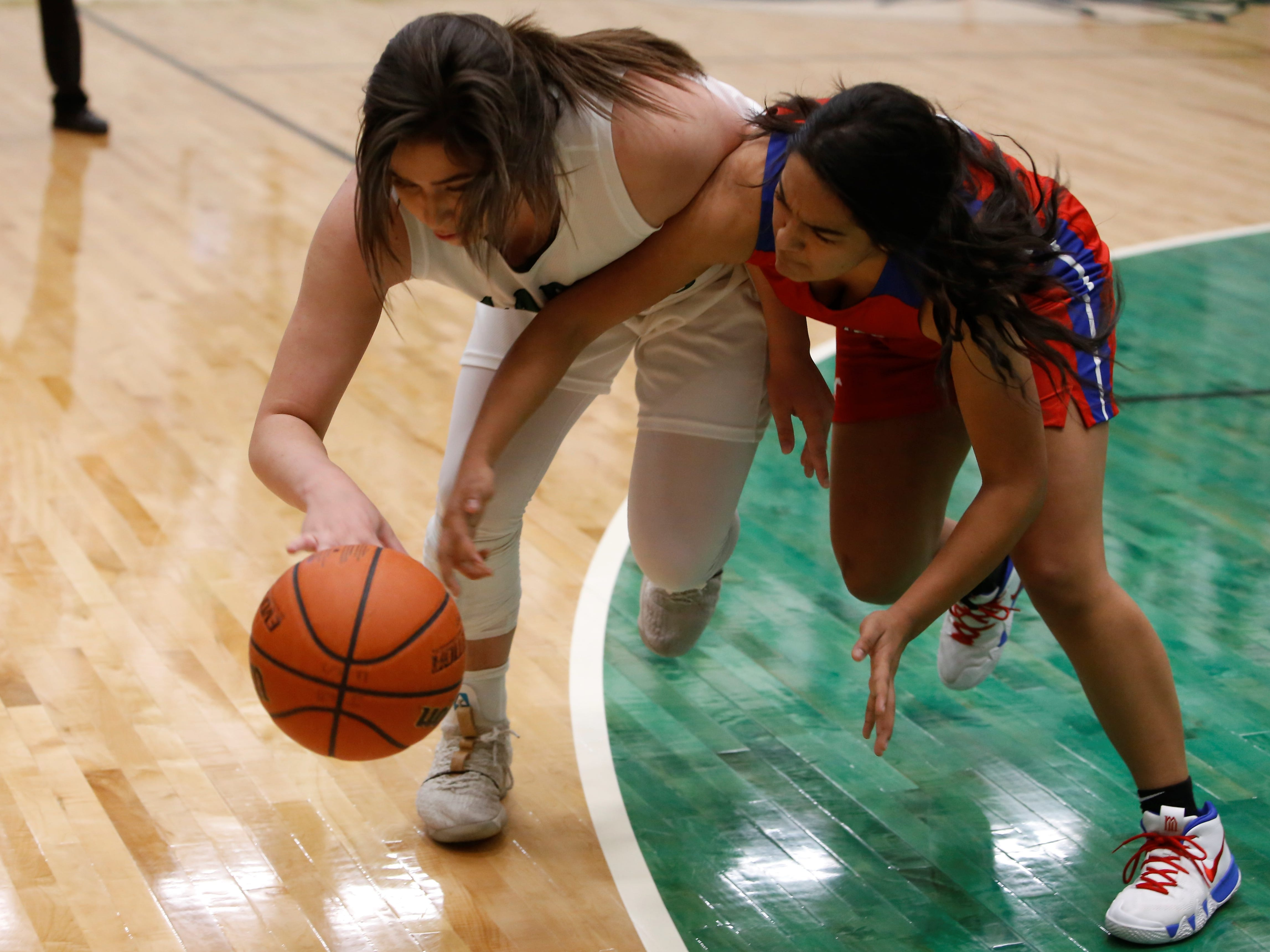 Farmington's Chloe Finch and West Mesa's Cece Barela fight for possession of the ball during Tuesday's District 2-5A game at Scorpion Arena in Farmington.
