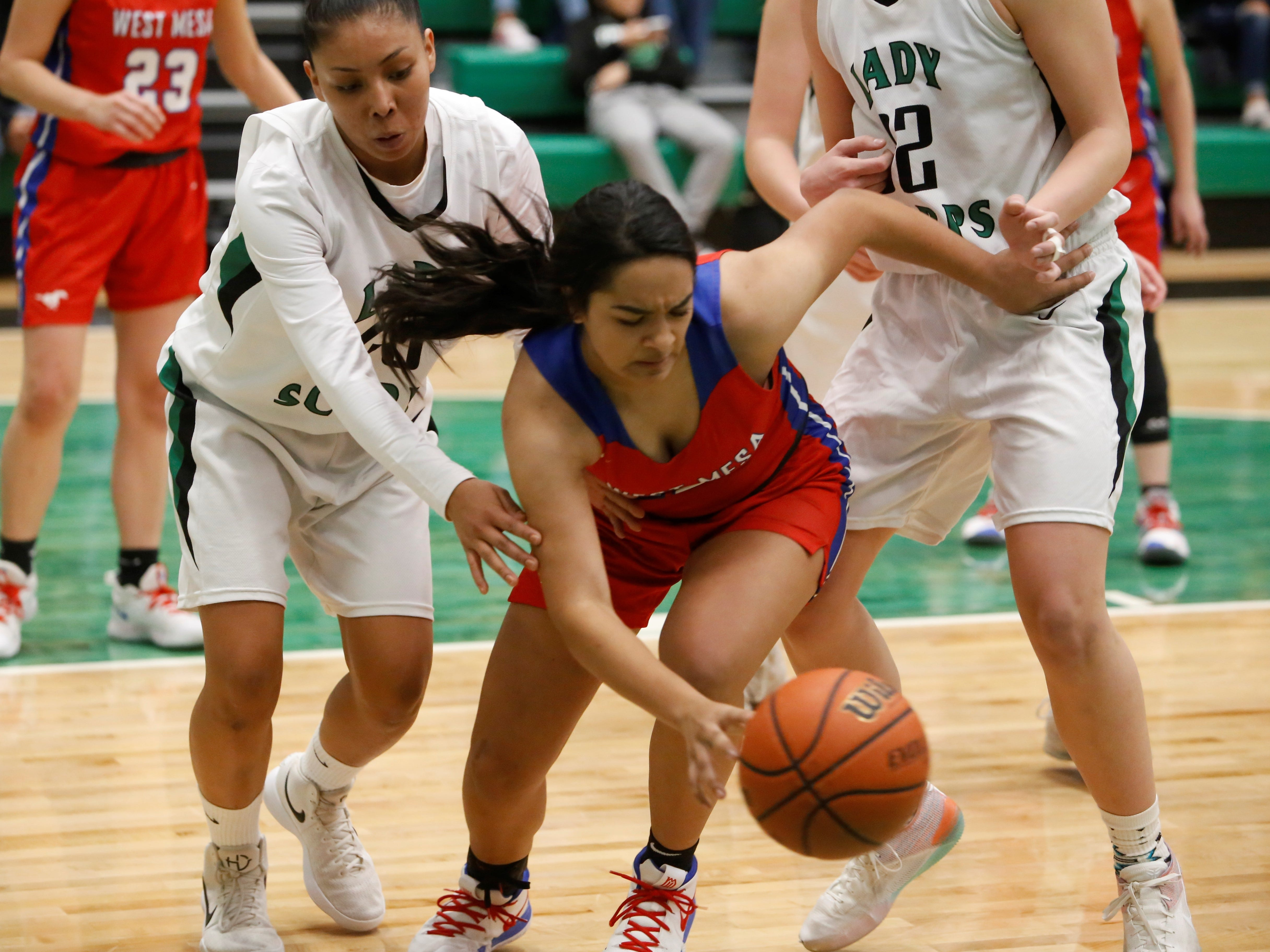 West Mesa's Cece Barela chases after a loose ball with Farmington's Davina Begay on her tail during Tuesday's District 2-5A game at Scorpion Arena in Farmington.