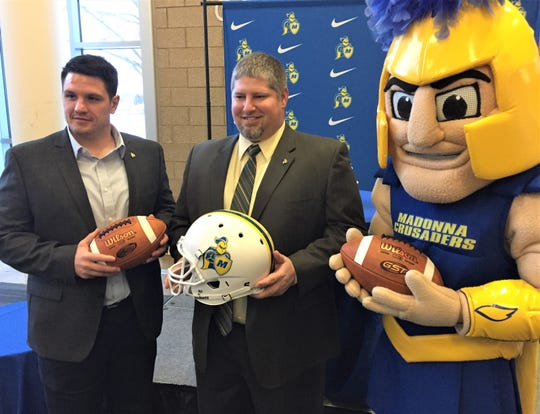 New Madonna football coach Brian Foos (center) and offensive coordinator Matt Wright (left) are greeted along with mascot Crusader.