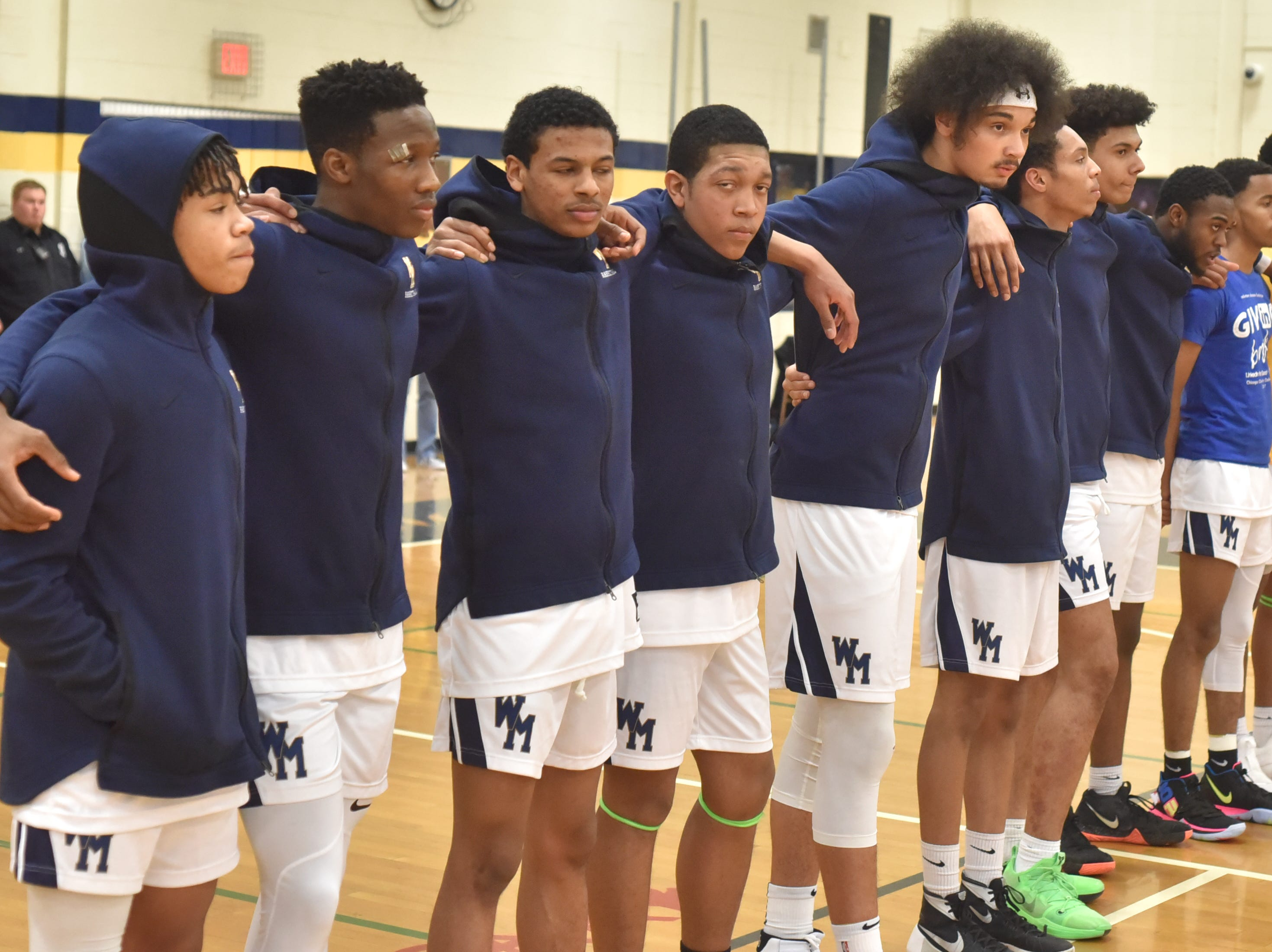 The Wayne Memorial boys varsity team stands together for the playing of the National Anthem.