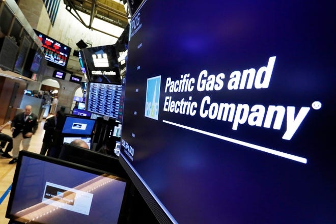 FILE- In this Jan. 14, 2019, file photo the logo for Pacific Gas & Electric Co. appears above a trading post on the floor of the New York Stock Exchange. Pacific Gas & Electric Co. says it expects capital spending of $6.6 billion this year and about $6.9 billion in 2020. PG&E made the disclosure in a filing with regulators on Wednesday, Jan. 23. (AP Photo/Richard Drew, File)