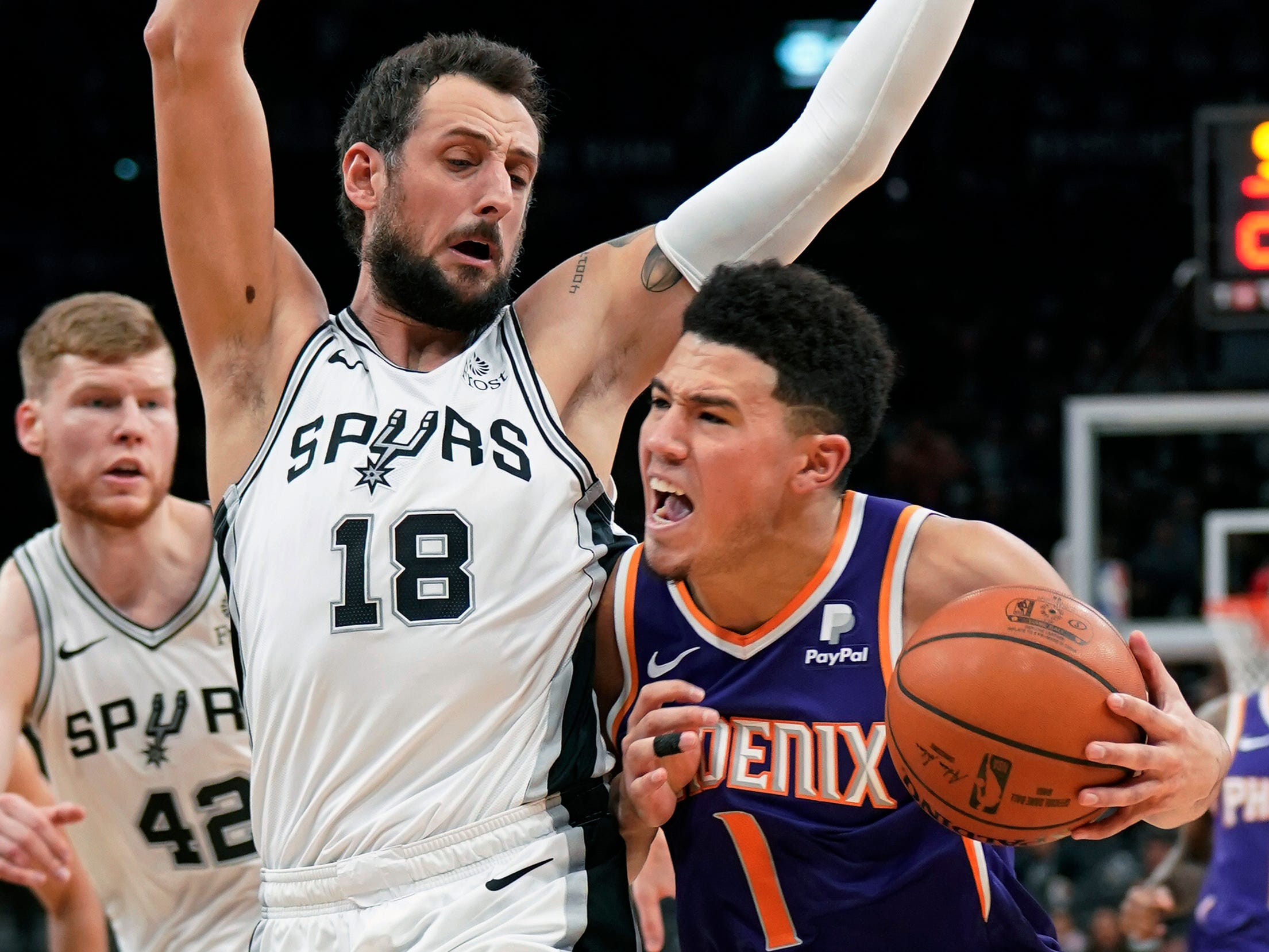 Phoenix Suns' Devin Booker (1) drives against San Antonio Spurs' Marco Belinelli during the first half of an NBA basketball game, Tuesday, Jan. 29, 2019, in San Antonio. (AP Photo/Darren Abate)