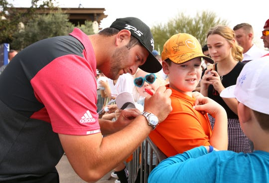 Former Arizona State Sun Devil and now PGA Tour star Jon Rahm signs the shirt of 10-year-old Bailey Dougherty from Cave Creek, Ariz., during the Annexus Pro-Am on Jan. 30 at the TPC Scottsdale Stadium Course.