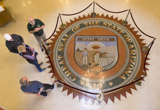 People are seen around the Arizona State Seal in the floor of the rotunda room at the Arizona State Capitol on Jan. 6, 2017.