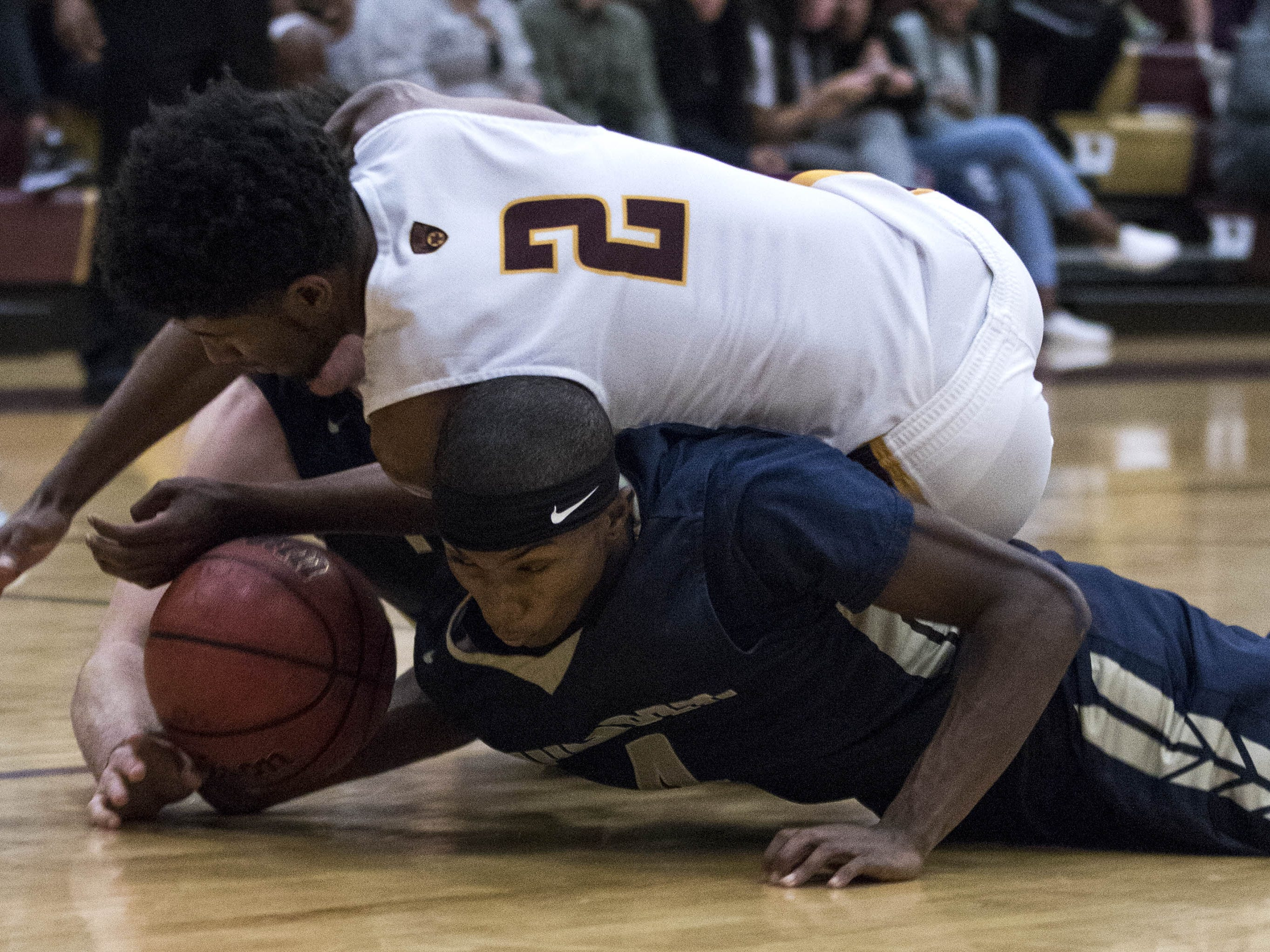 Mountain Pointe's Khalid Price (2) dives for a loose ball against Desert Vista's Isiah Wilson (4) and Mason Harbertson (1@) during their game in Phoenix on Tuesday, Jan. 29.