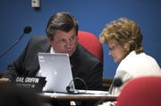Rep. Timothy M. Dunn talks with Rep. Gail Griffin during a hearing.