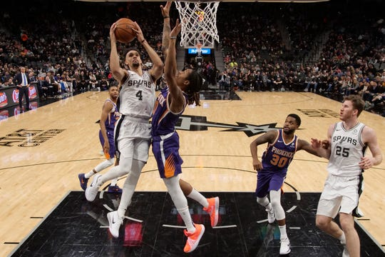 Spurs point guard Derrick White is fouled by Suns forward Emanuel Terry during the first half of a game Jan. 29 at AT&T Center.