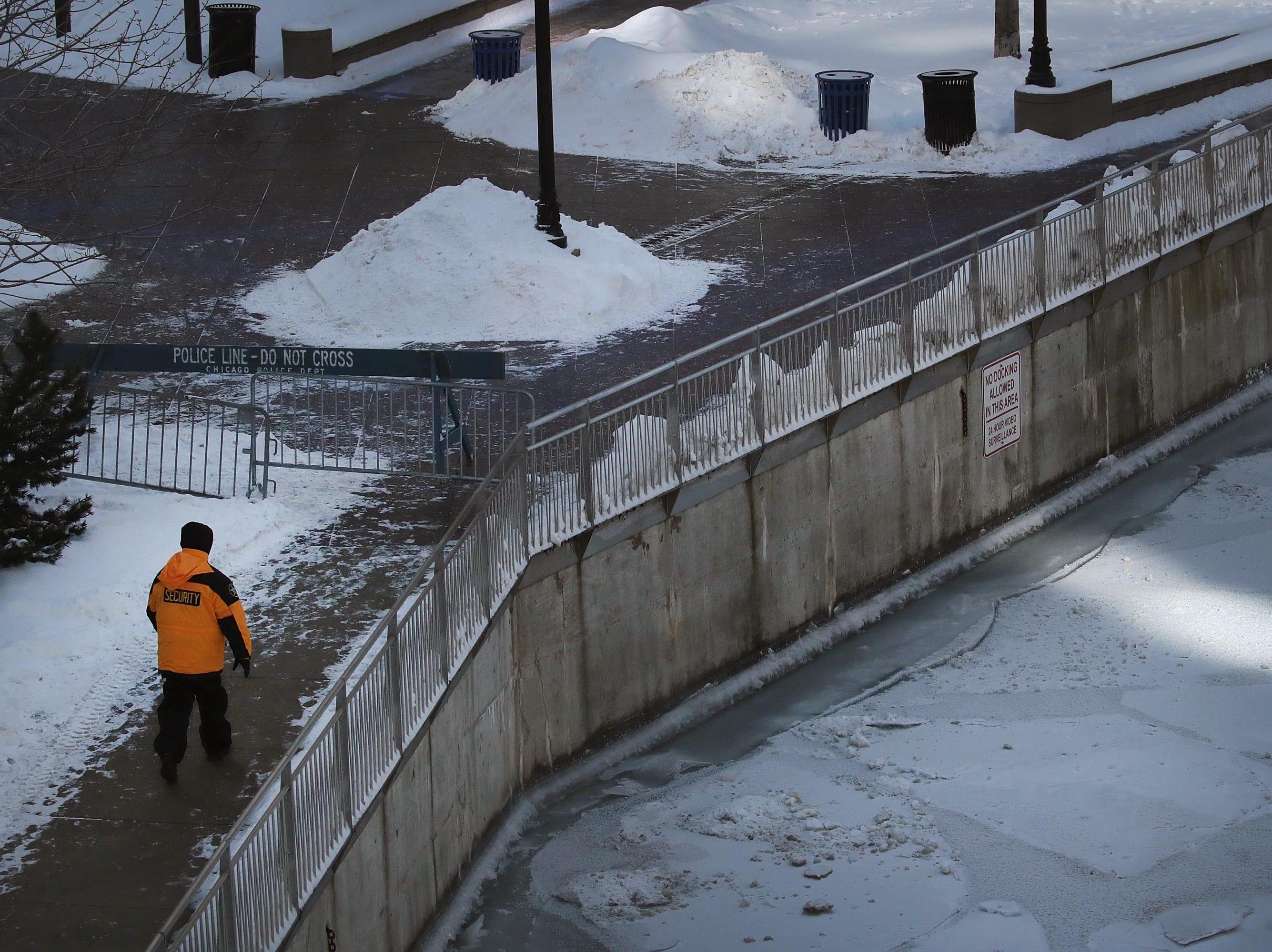 Un guardia de seguridad camina a lo largo del río Chicago congelado el 30 de enero de 2019 en Chicago, Illinois.