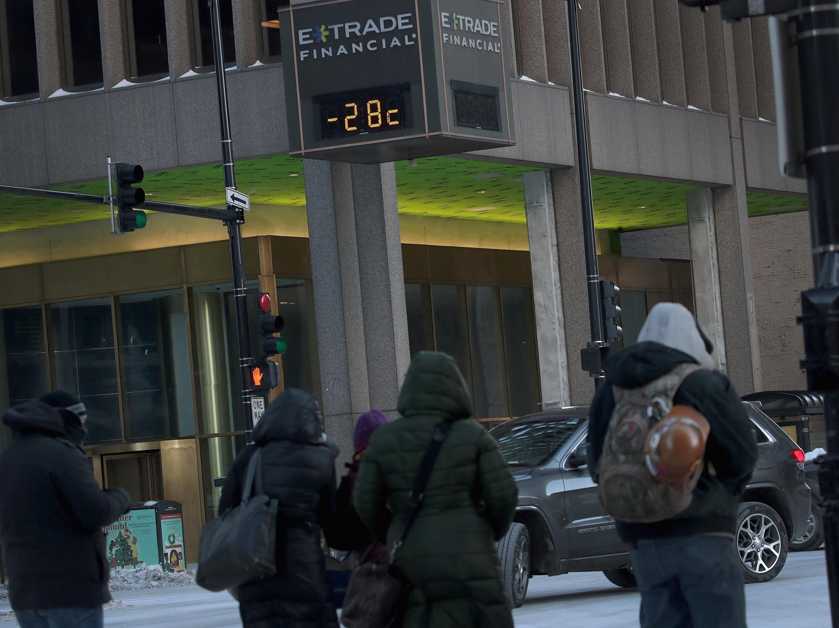 Transeuntes caminan cerca de un termómetro que registra -28 grados Celsius en el Loop el 30 de enero de 2019 en Chicago, Illinois.