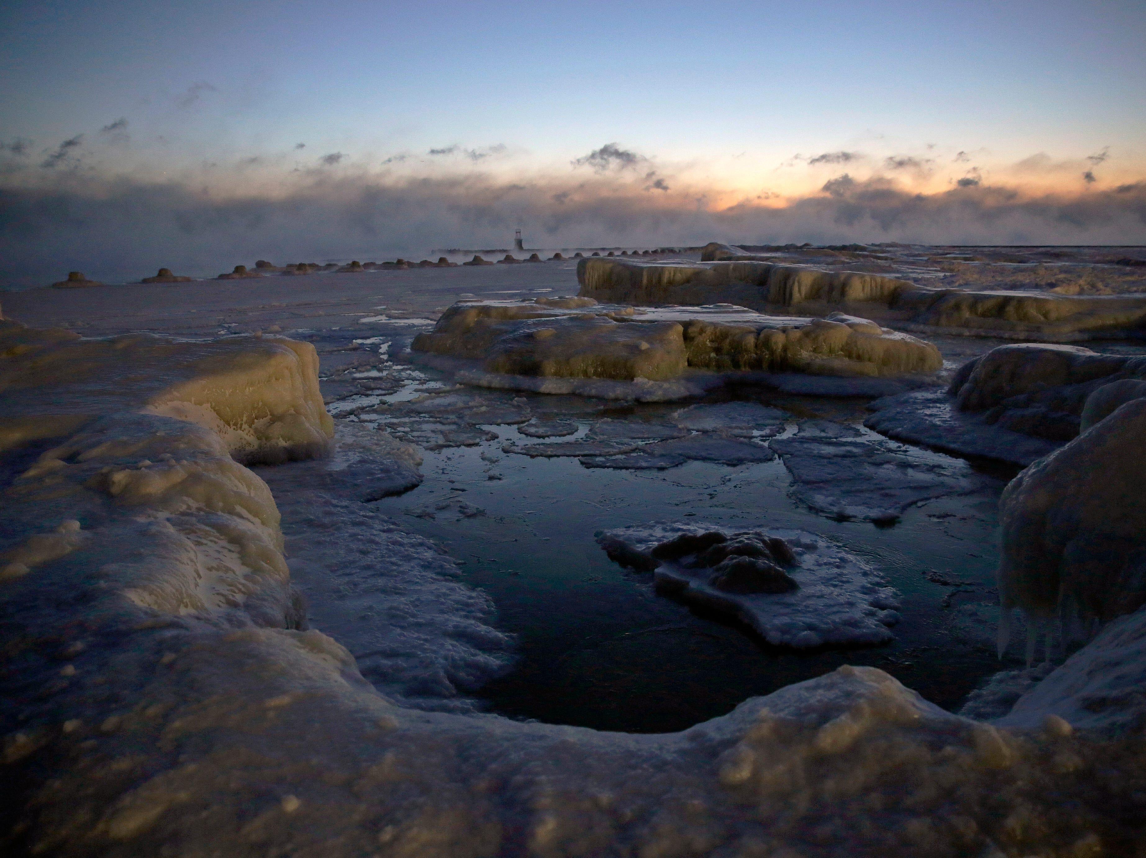 El hielo se forma a lo largo de la orilla del lago Michigan antes del amanecer, el miércoles 30 de enero de 2019, en Chicago.