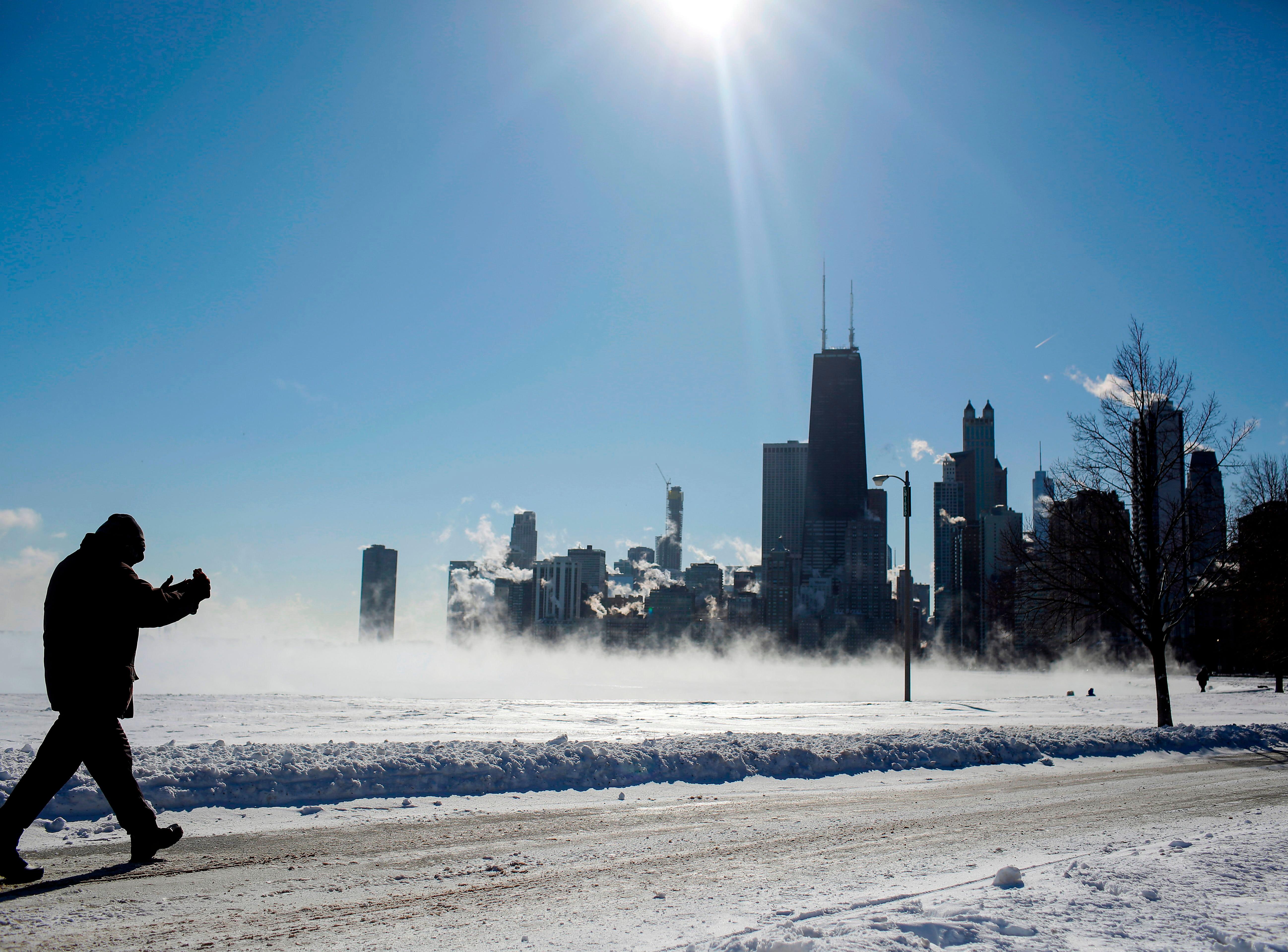 Un hombre toma una foto del lago Michigan y del horizonte cuando las temperaturas bajaron a -20 grados F (-29 C) el 30 de enero de 2019 en Chicago, Illinois.