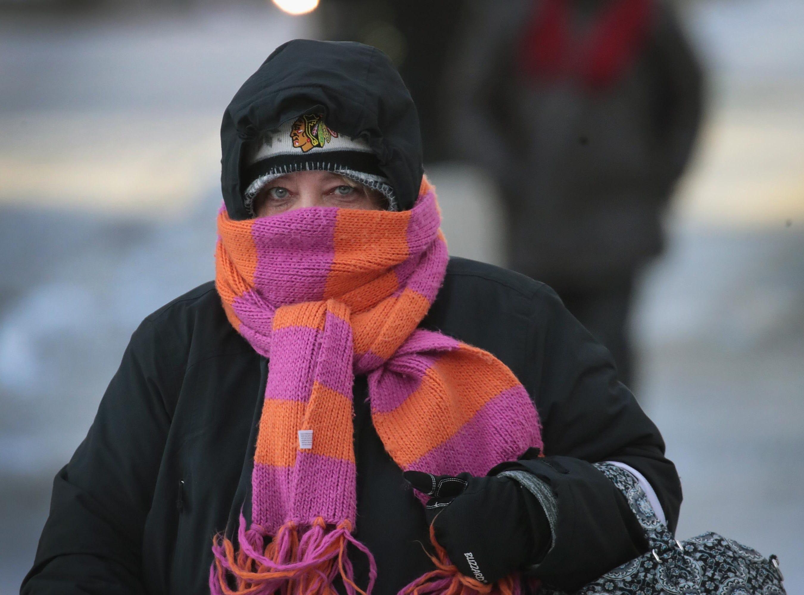 Una mujer camina por el centro de la ciudad en temperaturas bajo cero durante una hora punta de mañana extremadamente ligera el 30 de enero de 2019 en Chicago, Illinois.
